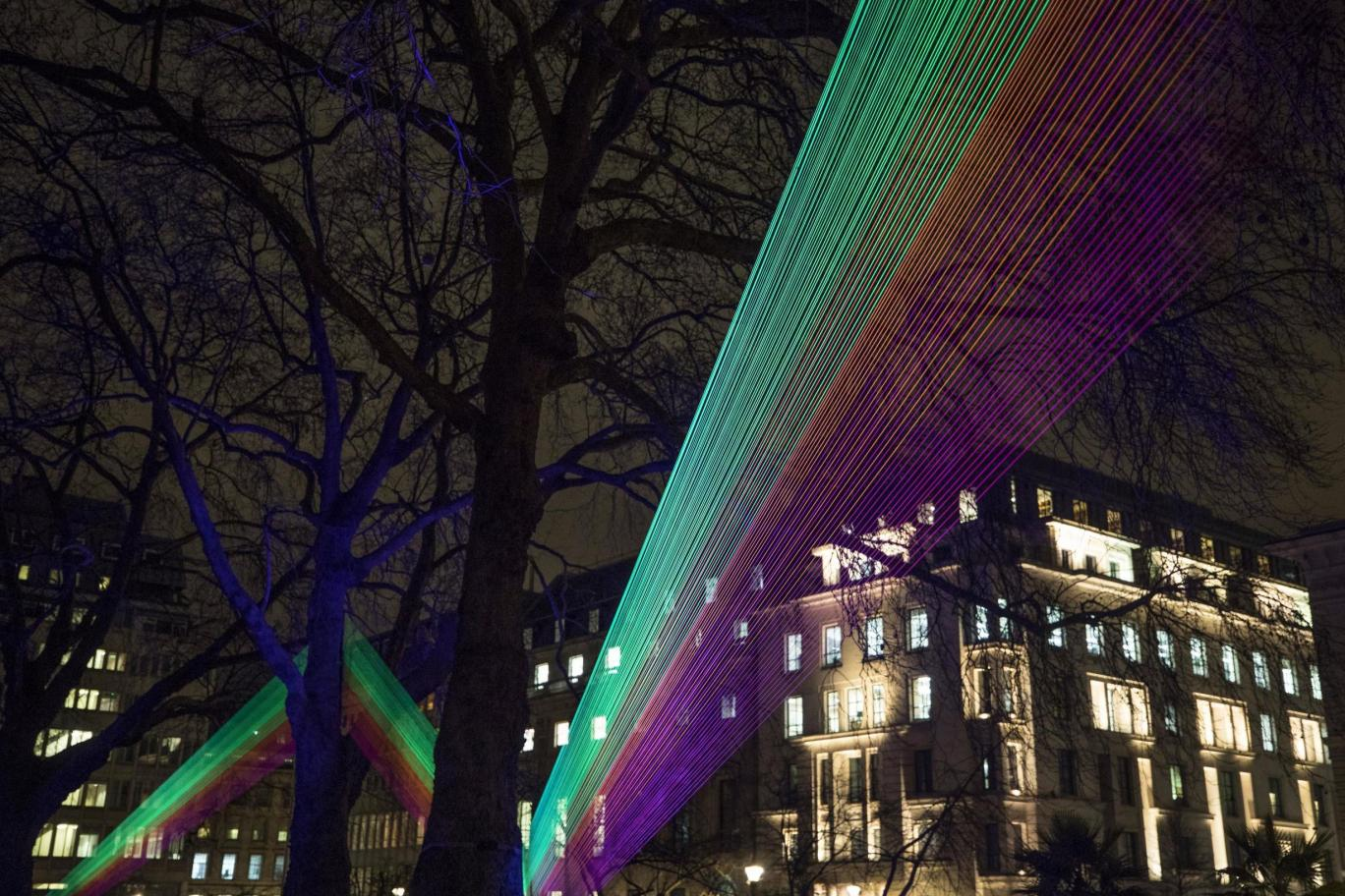 A rainbow of cord is illuminated to lead a path through the sky of St James Park
